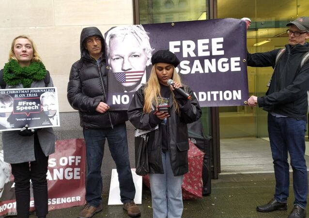 A girl reads out a poem by technologist Lauri Love, written in solidarity with Assange