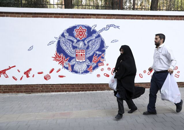 People walk past a satirical drawing of the Great Seal of the United States after new anti-U.S. murals on the walls of former U.S. embassy unveiled in a ceremony in Tehran, Iran, Saturday, Nov. 2, 2019