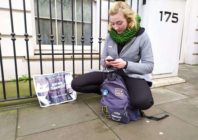 A student from Germany charges her phone having been outside court since 8 am.