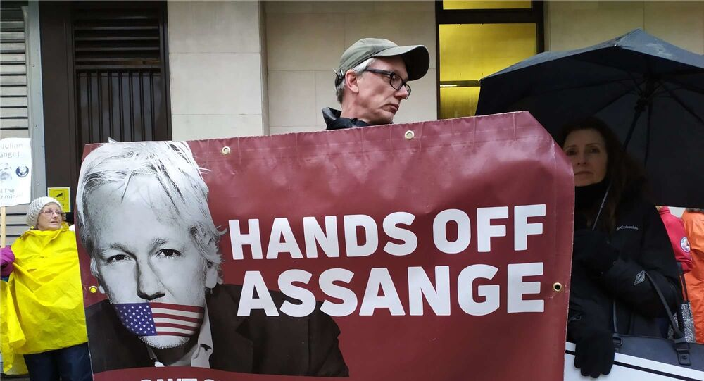 A man holds a banner at a rally in support of Assange in London