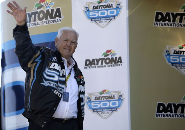 Former driver Junior Johnson waves to fans prior to the Daytona 500 NASCAR auto race at Daytona International Speedway