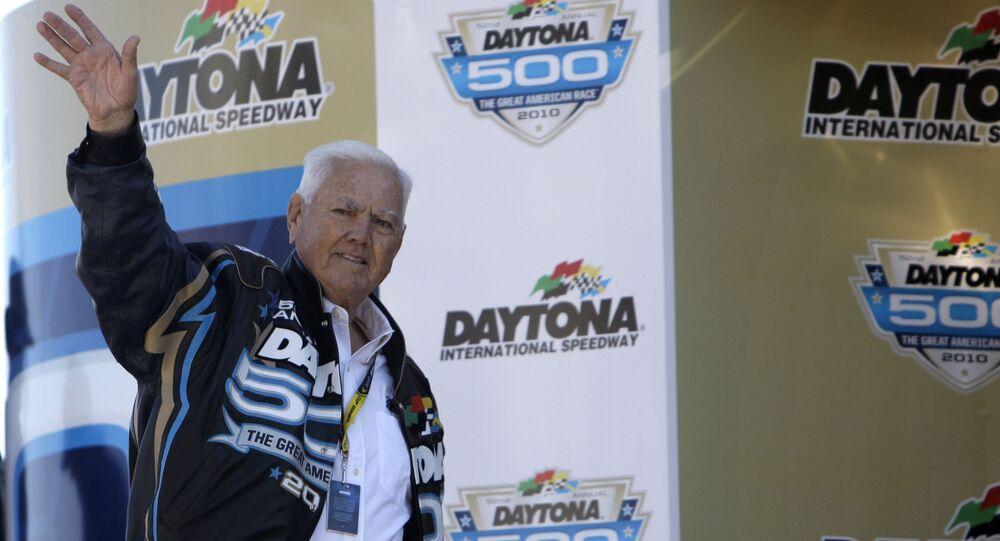 Former driver Junior Johnson waves to fans prior to the Daytona 500 NASCAR auto race at Daytona International Speedway