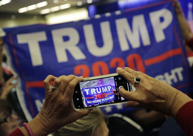 Supporters of President Donald Trump photograph a banner before a panel discussion with Donald Trump, Jr., Trump campaign senior adviser Kimberly Guilfoyle, and Trump campaign manager Brad Parscale, Tuesday, 15 October 2019, in San Antonio.