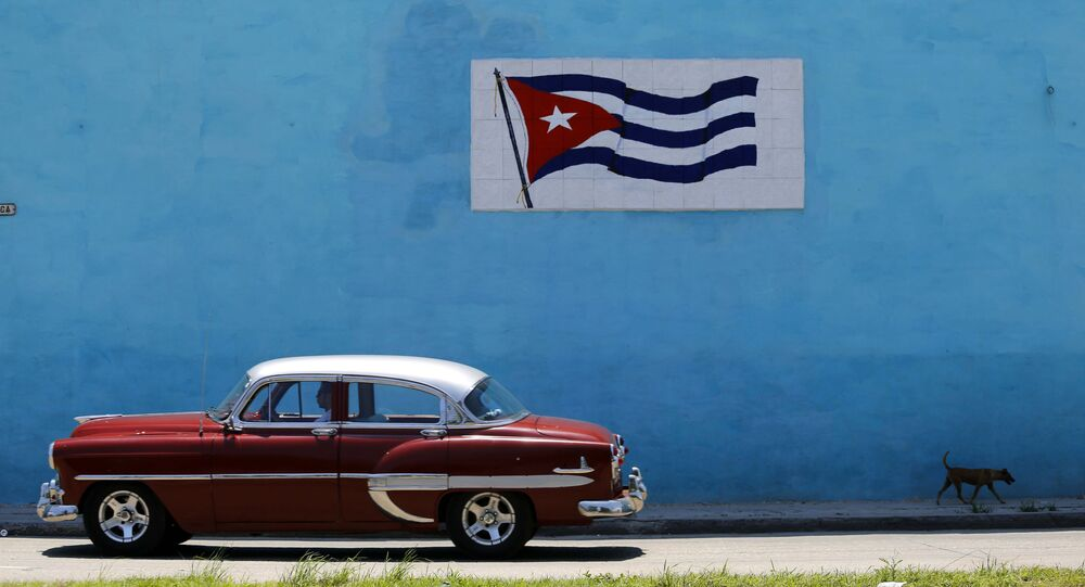 A driver steers his classic car past a wall decorated with a Cuban flag in Havana