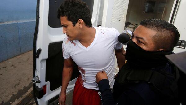A policeman escorts an inmate injured during a fight at El Porvenir prison, as they arrive at a hospital in Tegucigalpa, Honduras, December 22, 2019 - Sputnik International