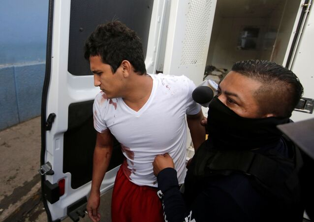 A policeman escorts an inmate injured during a fight at El Porvenir prison, as they arrive at a hospital in Tegucigalpa, Honduras, December 22, 2019
