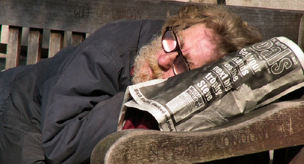 A homeless man resting on a bench in the City of London