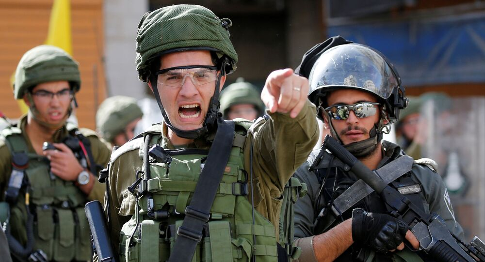 An Israeli soldier shouts during a protest as Palestinians call for a day of rage over U.S. decision on Jewish settlements, in Hebron in the Israeli-occupied West Bank November 26, 2019