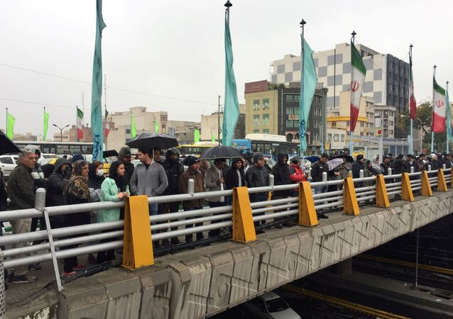 People stands in the street to show their protest against increased gas price in Tehran, Iran November 16, 2019