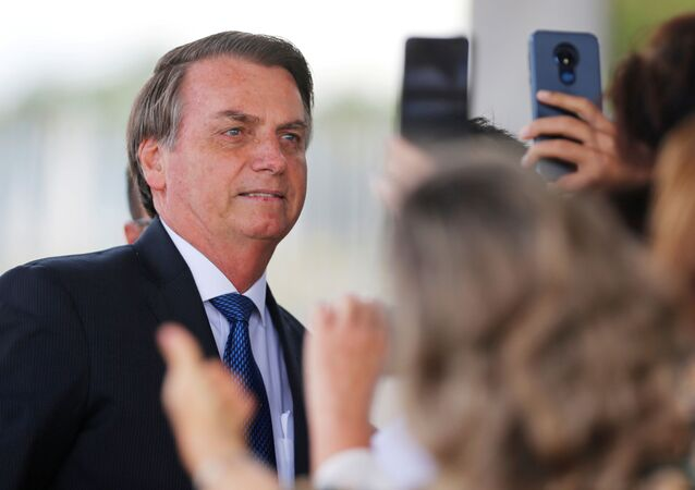 Brazil's President Jair Bolsonaro poses for pictures as he leaves the Alvorada Palace in Brasilia, Brazil December 12, 2019