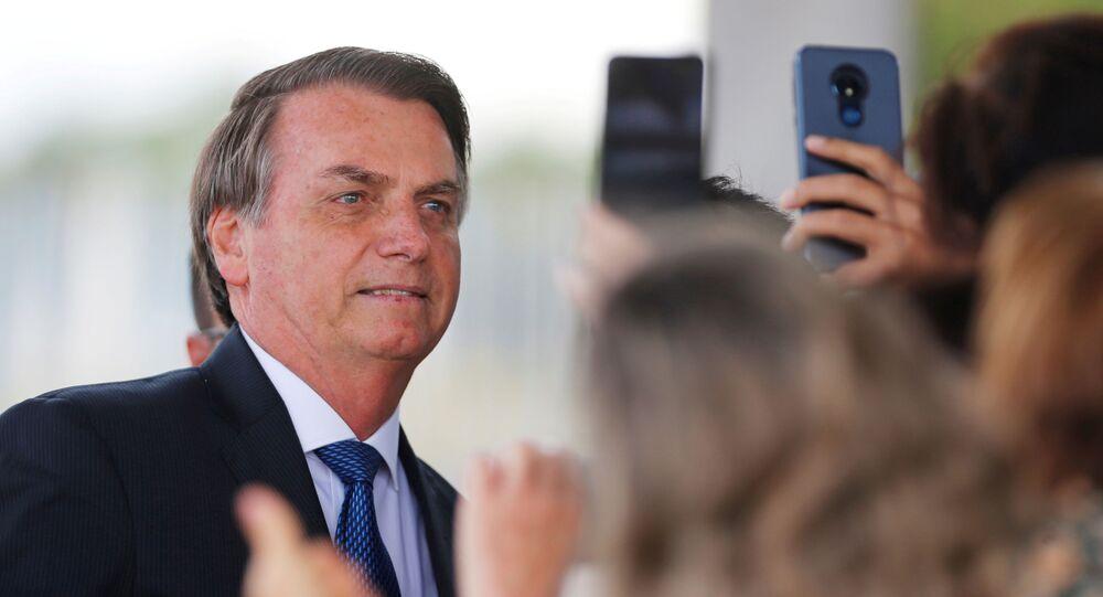 Brazil's President Jair Bolsonaro poses for pictures as he leaves the Alvorada Palace in Brasilia, Brazil December 12, 2019