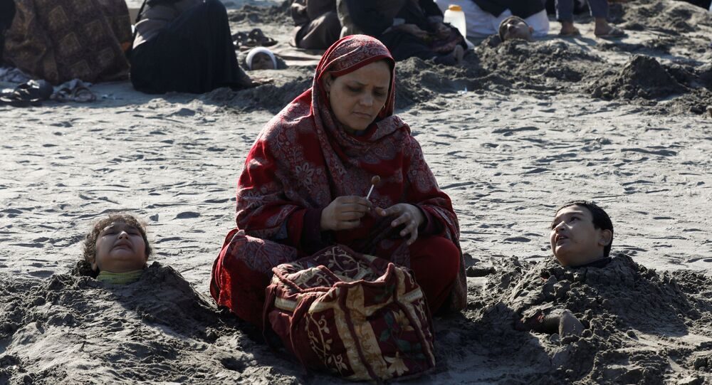 A woman sits near her children, buried up to their necks in sand during a solar eclipse, along Clifton beach in Karachi, Pakistan December 26, 2019