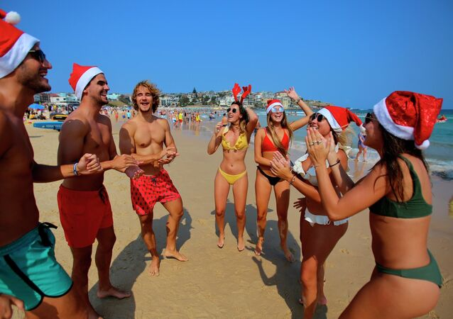 Tourists in Christmas costumes on a beach in Sydney