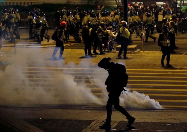 An anti-government demonstrator walks past tear gas on Christmas Eve in Hong Kong, China, December 24, 2019.