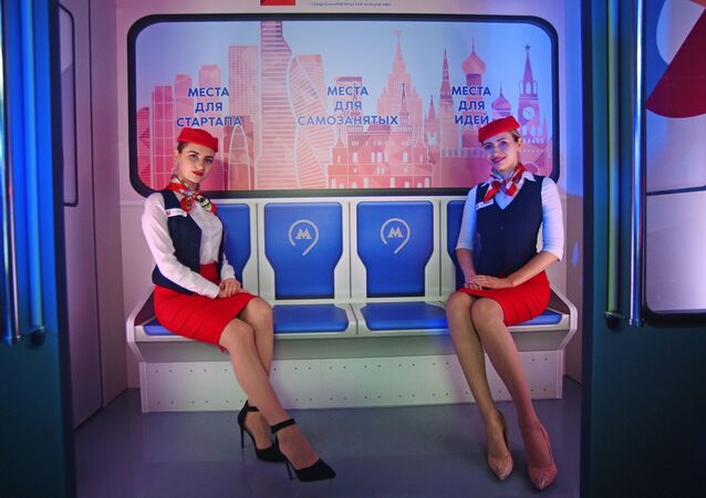Models dressed as Moscow metro employees pose for pictures in a themed Moscow Businessman train