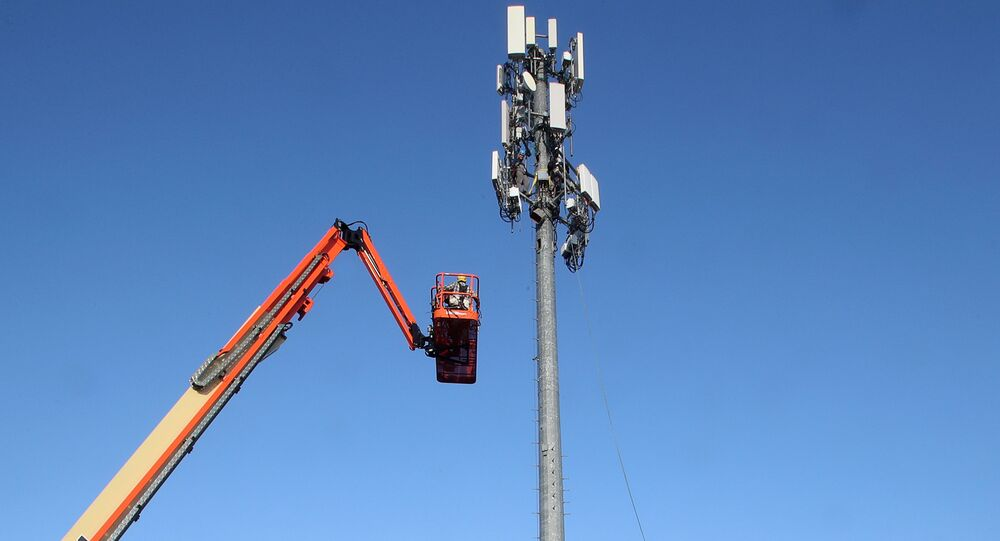 A contract crew from Verizon installs 5G telecommunications equipment on a tower in Orem, Utah, taken 3 December 2019