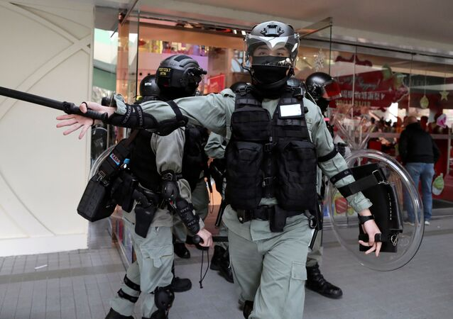 A riot police officer gestures as anti-government demonstrator take part in a protest in Sheung Shui shopping mall in Hong Kong, China, December 28, 2019