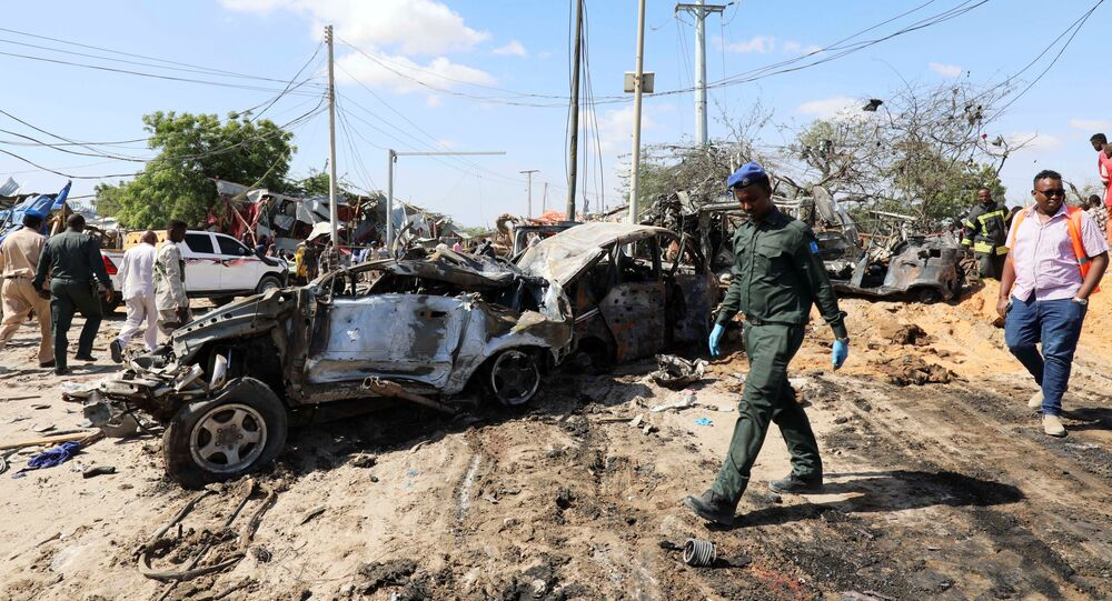 A Somali police officer walks past a wreckage at the scene of a car bomb explosion at a checkpoint in Mogadishu