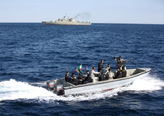 Iranian marine soldiers wave to the camera from a motor boat in the Sea of Oman during the third day of joint Iran, Russia and China naval war games