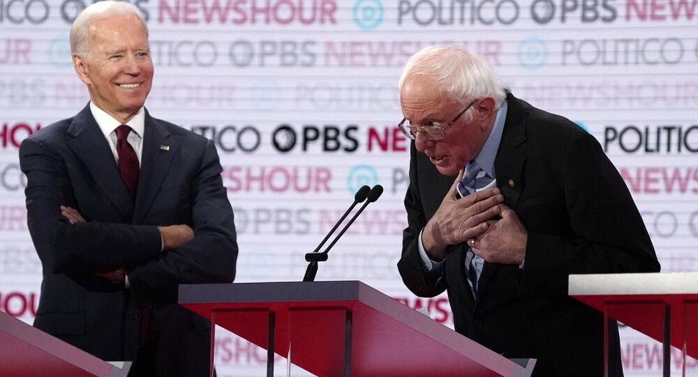 Former Vice President Joe Biden watches and listens to Senator Bernie Sanders speak towards the end of the sixth 2020 U.S. Democratic presidential candidates campaign debate at Loyola Marymount University in Los Angeles, California, U.S., December 19, 2019.