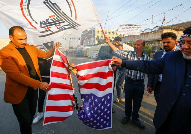 Iraqi people burn a U.S. flag in a protest after an airstrike at the headquarters of Kataib Hezbollah militia group in Qaim