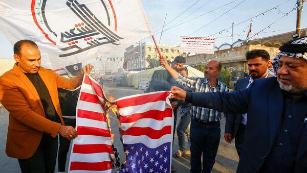 Iraqi people burn a U.S. flag in a protest after an airstrike at the headquarters of Kataib Hezbollah militia group in Qaim - Sputnik International