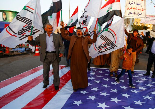 Iraqi people walk on a U.S. flag in a protest after an airstrike at the headquarters of Kataib Hezbollah militia group in Qaim, in the holy city of Najaf, Iraq December 30, 2019.