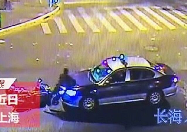 A drunk man threw himself on to a taxi in Shanghai, China imitating a fall in an insurance scam.