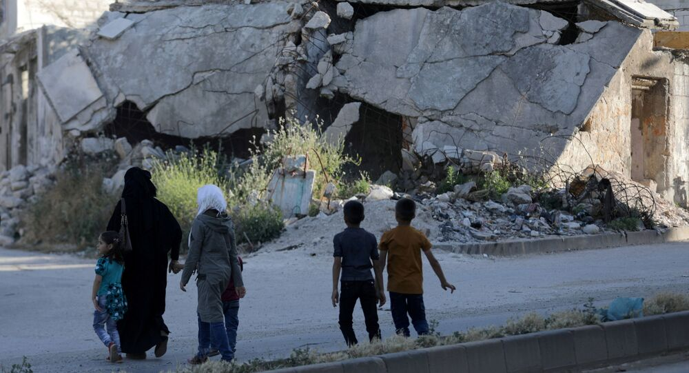 People walk near rubble of damaged buildings in the city of Idlib, Syria May 27, 2019. Picture taken May 27, 2019.