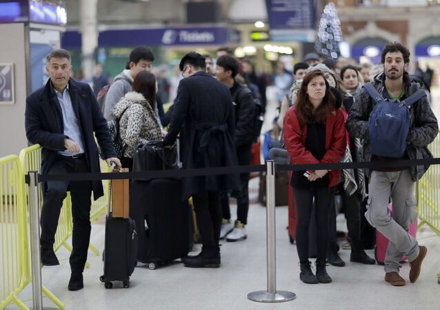 UK Passengers wait at the front of a queue for the next express train to Gatwick Airport