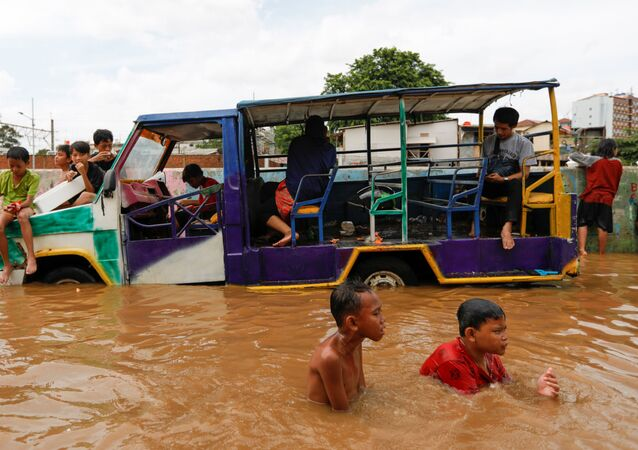 Children play at an area flooded after heavy rains in Jakarta, Indonesia