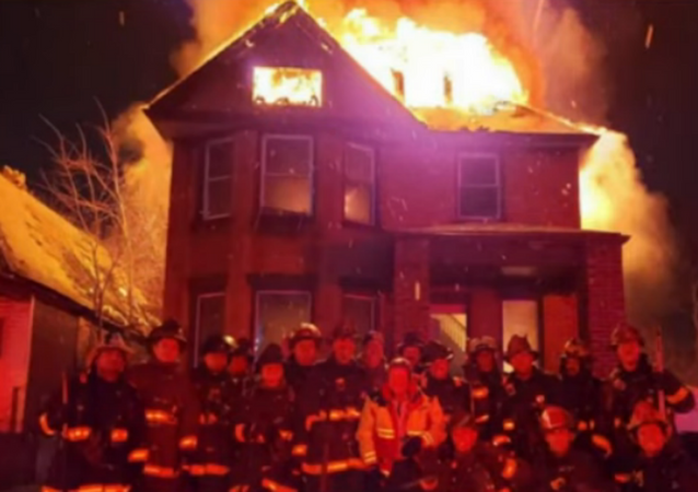 Officials with Michigan's Detroit Fire Department have come under fire after posing for a picture in front of a burning, vacant home to celebrate the retirement of a battalion chief.