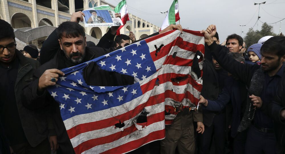Protesters burn a U.S. flag during a demonstration over the U.S. airstrike in Iraq