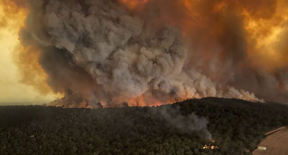 In this Monday, Dec. 30, 2019, aerial photo, wildfires rage under plumes of smoke in Bairnsdale, Australia. Thousands of tourists fled Australia's wildfire-ravaged eastern coast ahead of worsening conditions as the military started to evacuate people trapped on the shore further south.