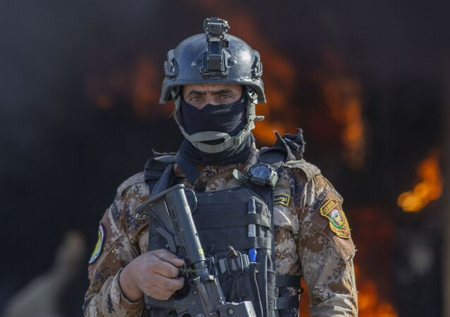 An Iraqi soldier stands guard in front of smoke rising from a fire set by pro-Iranian militiamen and their supporters at the US embassy compound in Baghdad, Iraq, Wednesday, 1 January 2020.