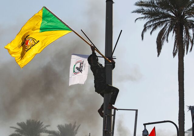 A member of the Hashd al-Shaabi paramilitary forces holds a flag of the Kataib Hezbollah militia group during a protest to condemn air strikes on their bases, in Baghdad, Iraq, 31 December 2019.