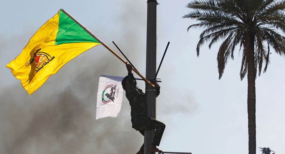 A member of Hashd al-Shaabi (paramilitary forces) holds a flag of Kataib Hezbollah militia group during a protest to condemn air strikes on their bases, in Baghdad, Iraq December 31, 2019.