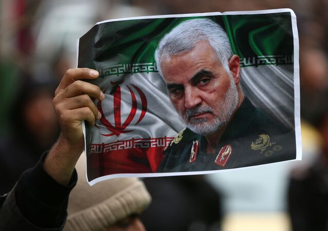 An Iranian in Tehran holds a picture of the late general Qassem Soleimani, head of the elite Quds Force, who was killed in a drone strike at Baghdad International Airport, 4 January 2020.