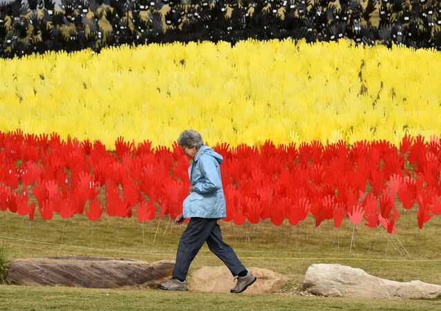 A woman passes a huge art installation called 'Sea of Hands' which consists of thousands of hands in the colours of the Aboriginal flag – red, yellow, black. - Part of National Reconciliation Week 2016, the installation is for Australians to reflect on Australia's national identity and the place of Aboriginal and Torres Strait Islander histories and cultures in the nation's story.