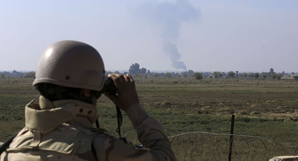 In this Tuesday, Nov. 13, 2018 photo, an Iraqi soldier watches smoke rising after an airstrike by US-led International coalition warplanes against ISIS, on the border between Syria and Iraq in Qaim, Anbar province, Iraq.
