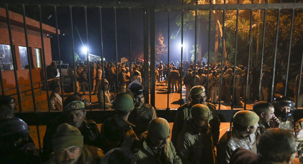 In this late Sunday, Jan.5, 2020 photo, police arrive at the Jawaharlal Nehru University after masked assailants beat students and teachers with sticks in New Delhi, India.