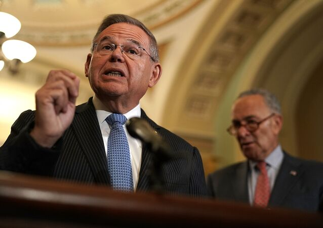 U.S. Sen. Bob Menendez speaks as Senate Minority Leader Sen. Chuck Schumer listens during a news briefing