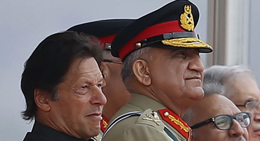 In this March 23, 2019 photo, Pakistan's Army Chief Gen. Qamar Javed Bajwa, center, watches a parade with Prime Minister Imran Khan, left, and President Arif Alvi, in Islamabad, Pakistan.