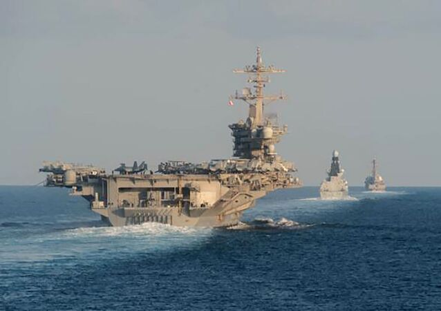 In this Tuesday, Nov. 19, 2019, photo made available by U.S. Navy, the aircraft carrier USS Abraham Lincoln, left, the air-defense destroyer HMS Defender and the guided-missile destroyer USS Farragut transit the Strait of Hormuz with the guided-missile cruiser USS Leyte Gulf.