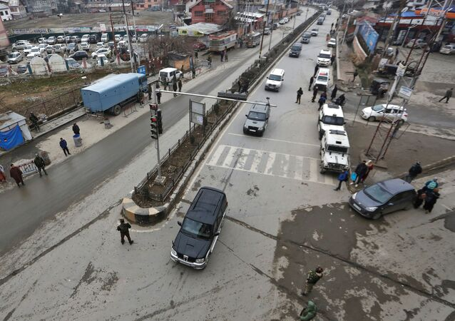 Indian security personnel stand guard as a convoy believed to be transferring foreign diplomats moves in Srinagar, January 9, 2020