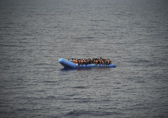 Migrants aboard a blue plastic boat in the Mediterranean Sea