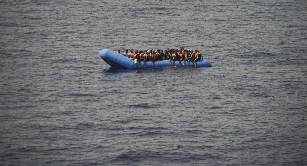 Migrants aboard a blue plastic boat in the Mediterranean Sea