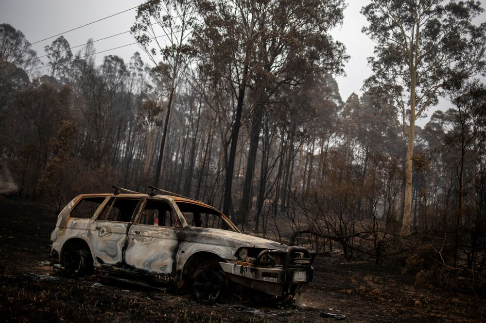 A destroyed car is seen next to burnt bushland in the village of Mogo, Australia on 8 January 2020.