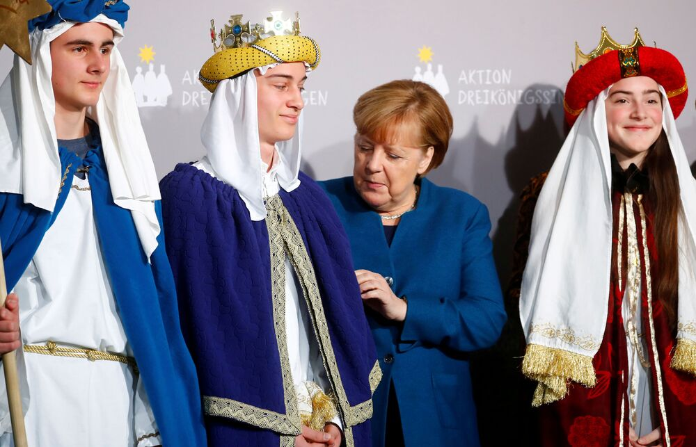 German Chancellor Angela Merkel meets carol singers during a reception at the German Chancellery in Berlin, Germany, 7 January 2020.