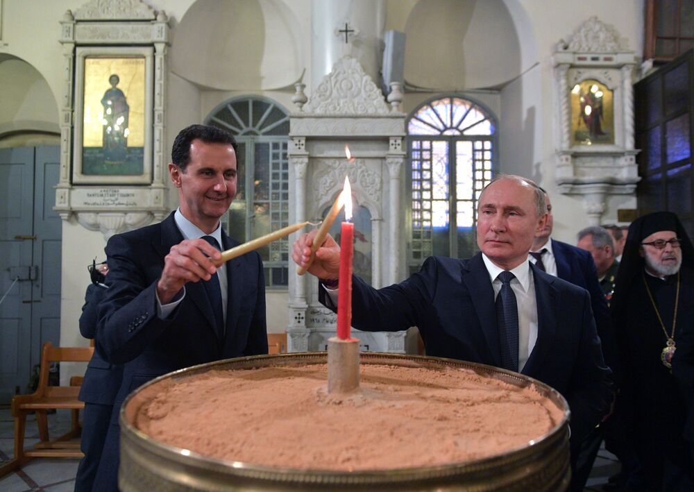 Russian President Vladimir Putin and his Syrian counterpart Bashar al-Assad at a Damascus cathedral, 7 January 2020.